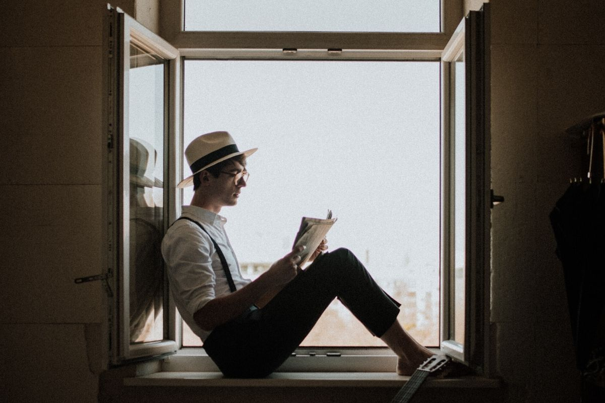 Man reading on window seat