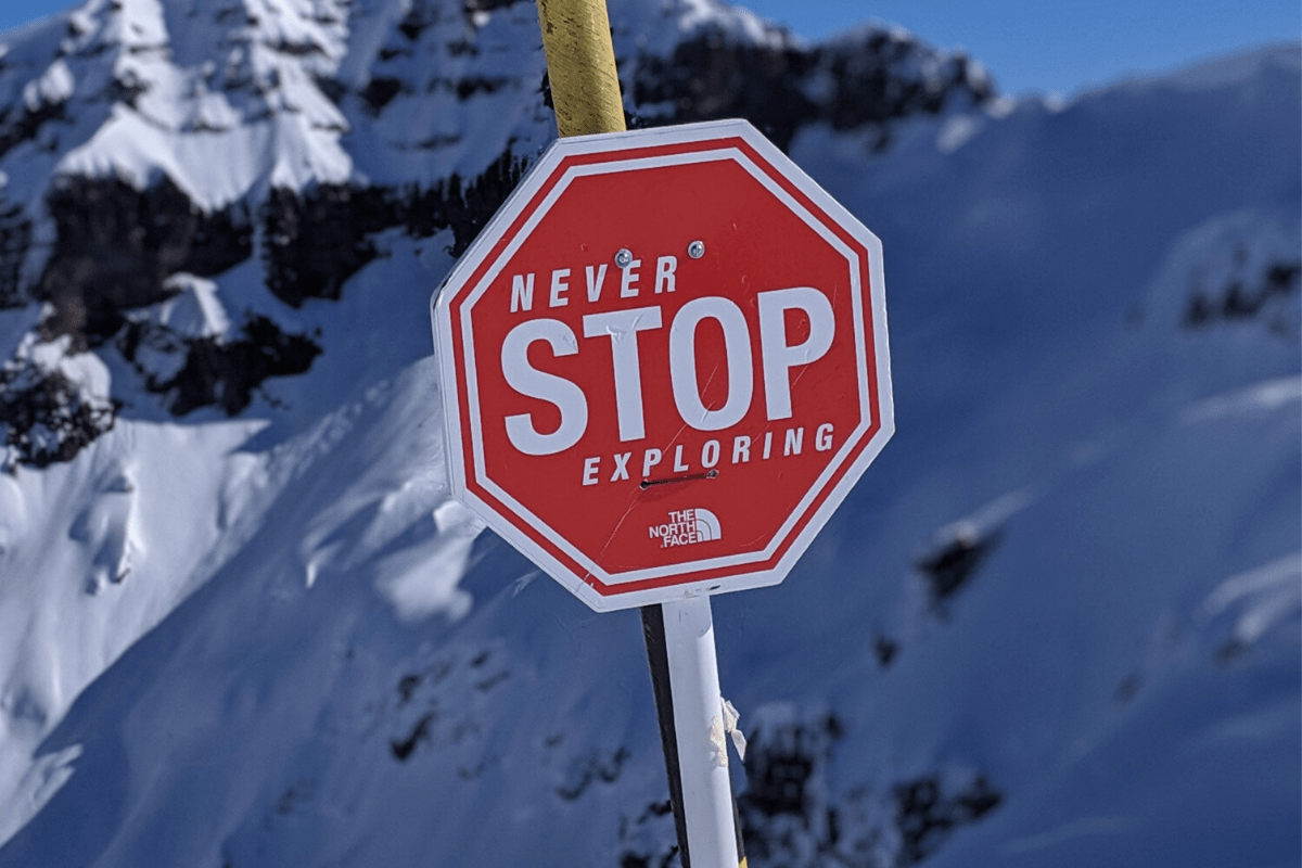 Never stop exploring sign in the mountains