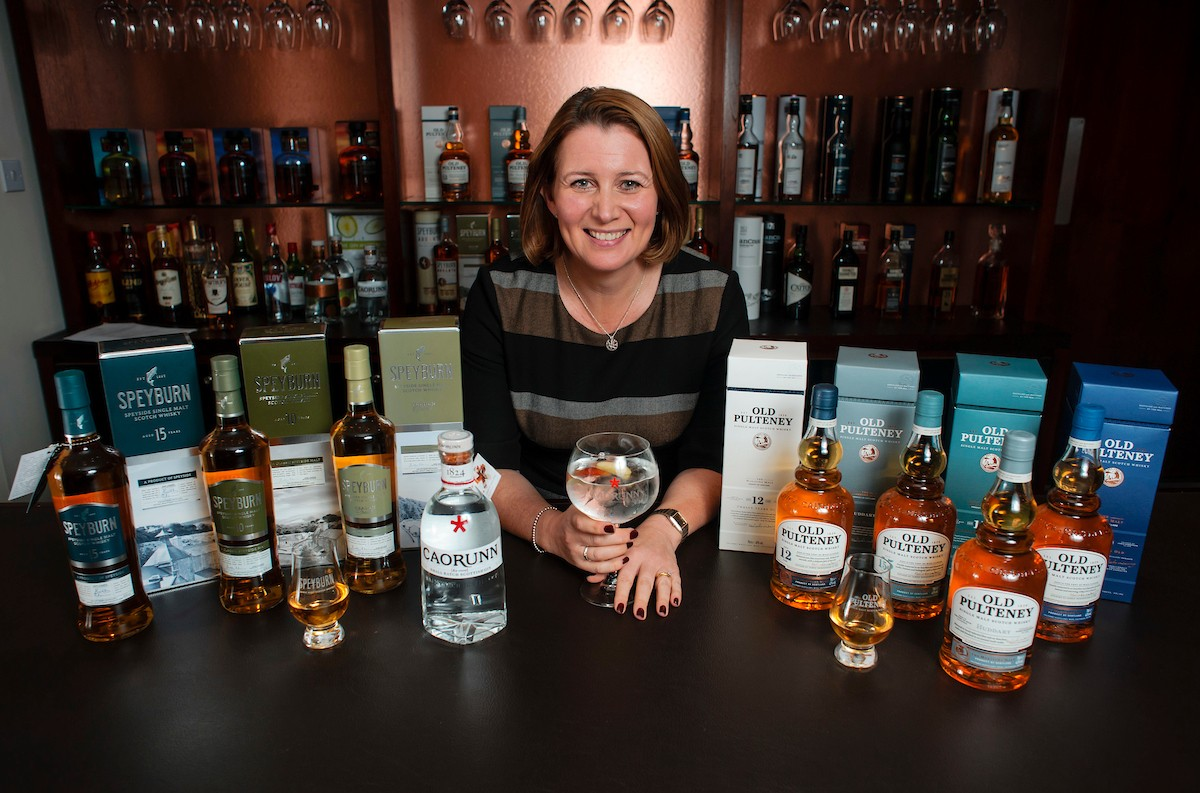 woman smiling surrounded by spirits bottles