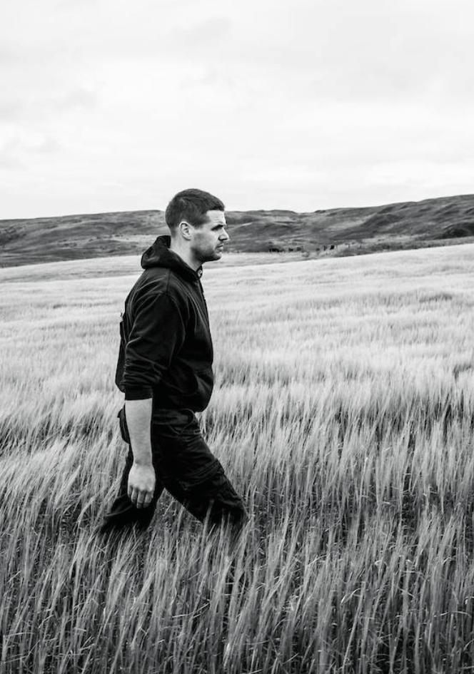 man walking across wheat field